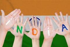 Надпись Индии на руках детей на фоне развевая флага Индии стоковые фотографии rf