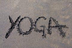 Надпись йоги нарисованная на черном и коричневом песке стоковая фотография