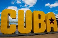 Надпись КУБЫ Огромные письма на портовом районе, против голубого неба с облаками в Сантьяго-де-Куба стоковое фото rf