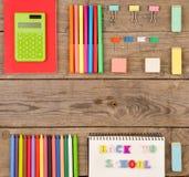 надпись & x22; назад к school& x22; , калькулятор, блокноты, отметки и другие канцелярские принадлежности на коричневом деревянно стоковые изображения rf