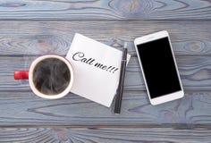 Надпись на салфетке вызывает меня Телефон и кофе в красной чашке Стоковое Изображение RF