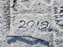 Надпись 2019 на снеге Надпись и хворостина на снеге стоковое изображение rf