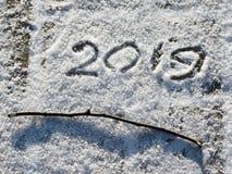 Надпись 2019 на снеге Надпись и хворостина на снеге стоковое фото rf