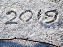 Надпись 2019 на снеге Надпись и хворостина на снеге стоковое изображение