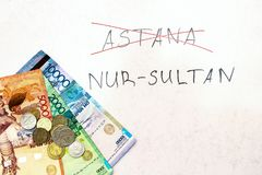 Надпись пересекла вне Астану, и имя нового города Nursultan, на естественной белой предпосылке с валютой  стоковое изображение