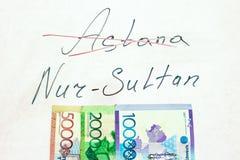 Надпись пересекла вне Астану, и имя нового города Nursultan, на естественной белой предпосылке с валютой  стоковое фото