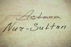 Надпись пересекла вне Астану, и имя нового города Nursultan, на естественной белой предпосылке с валютой  стоковое фото rf