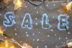 Надпись продажи на предпосылке рождества Новый Год украшения на бумаге kraft Коробки рождества в снеге с Стоковые Изображения