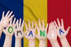 Надпись Румынии на руках детей на фоне развевая флага Румынии стоковые фотографии rf
