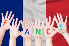 Надпись Франции на руках детей на фоне развевая флага Франции стоковая фотография
