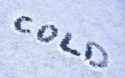 """Надпись """"холодная """"на снежном стекле стоковое изображение"""