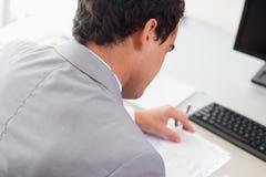 Над взглядом бизнесмена делая обработку документов Стоковое Изображение