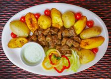 Над взглядом зажаренного мяса с, картошка, сладостные томаты, sald, перец, зажарила подорожник, который служат в белой плите над  Стоковое Изображение
