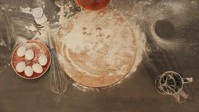 над взглядом Крупный план женских рук положил свежий хлеб на таблицу Мука разбросана вокруг Яйца лежат на красном цвете видеоматериал