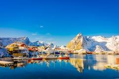 Над взглядом некоторых деревянных зданий в заливе с шлюпками в береге в островах Lofoten окруженных с снежным Стоковые Изображения