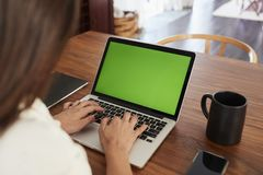Над взглядом плеча женщины сидя на таблице используя ноутбук дома, конец вверх стоковые изображения rf