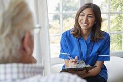 Над взглядом плеча медсестры на домашнем посещении с старшим человеком стоковое фото rf