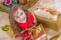 Над взглядом счастливой девушки нося красную блузку и держа шарик рождества, украшения и подарка в ее руках, рождества Стоковые Изображения RF