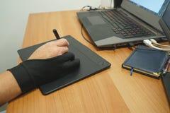 Над взглядом таблетки графиков пользы руки человека дизайнерской с экраном касания стоковые фотографии rf