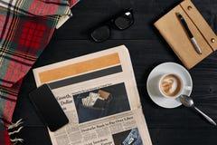 Над взглядом умного телефона, газеты, шарфа в клетке, стекел с тетрадью и чашки кофе latte на черное деревянном Стоковые Изображения