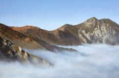 над пиками горы облаков Стоковые Фото