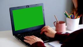 Над плечом снял женщины печатая на компьтер-книжке с ключ-зеленым экраном сток-видео