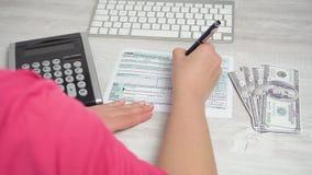 Над съемкой плеча налоговой формы 1040 завалки женщины на столе рядом с клавиатурой и калькулятором компьютера видео 4K видеоматериал