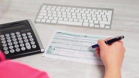 Над съемкой плеча налоговой формы 1040 чтения женщины и расчетливого возврата налога на столе рядом с клавиатурой компьютера видеоматериал