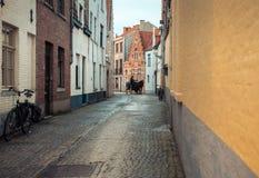 Наездник на узкой улице в Брюгге, Бельгии Стоковые Фотографии RF