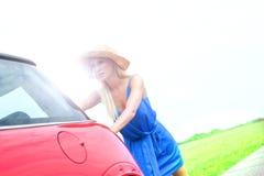Нажатие женщины сломанное вниз с автомобиля на проселочной дороге против ясного неба Стоковые Фото