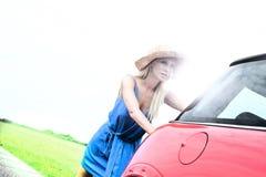Нажатие женщины сломанное вниз с автомобиля на проселочной дороге против ясного неба Стоковое фото RF
