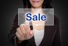 Нажим женщины к кнопке продажи на виртуальном экране стоковое фото