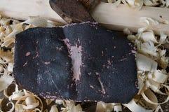 Наждачная шкурка, старый молоток, доска и деревянные shavings Стоковое фото RF