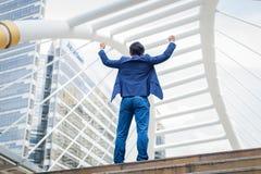 Назад азиатской стойки бизнесмена и поднимать вверх руки отпраздновал его успешное в карьере и полете стоковые фотографии rf