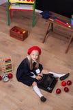 Назад в школу! Девушка в берете сидит с машинкой и учит в классе На классн классном в украинском языке w стоковая фотография
