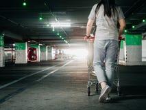 Назад женщины с движением магазинной тележкаи и ищите ее автомобиль в ca Стоковое фото RF