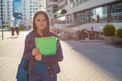 Назад к девушке подростка студента школы держа книги и блокноты нося рюкзак r стоковые изображения