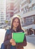 Назад к девушке подростка студента школы держа книги и блокноты нося рюкзак r стоковые фото