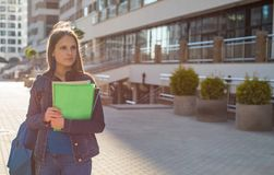 Назад к девушке подростка студента школы держа книги и блокноты нося рюкзак r стоковые изображения rf