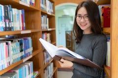 Назад к концепции университета коллежа знания школьного образования, красивый женский студент колледжа держа ее книги усмехаясь с стоковые изображения