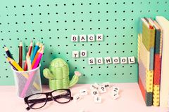 Назад к месту для работы школьных принадлежностей пастельному с карандашами, стекла, кактусы вычисляют и деревянные письма на дос Стоковая Фотография