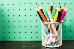 Назад к месту для работы школьных принадлежностей пастельному с карандашами, цепь единорога ключевая Стоковые Изображения RF