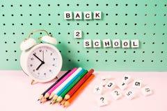 Назад к месту для работы школьных принадлежностей пастельному с карандашами и деревянными письмами на доске Стоковые Фото