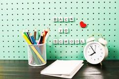 Назад к месту для работы школьных принадлежностей пастельному с ультрамодными деталями и деревянными письмами на доске Стоковая Фотография RF