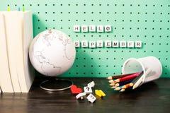 Назад к месту для работы школьных принадлежностей пастельному с ультрамодными деталями, глобусом и деревянными письмами на доске Стоковые Изображения