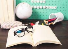 Назад к месту для работы школьных принадлежностей пастельному с ультрамодными деталями, глобусом, стеклами и книгами и деревянным Стоковые Фото