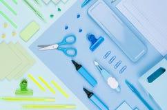 Назад к предпосылке школы - покрашенные различные канцелярские принадлежности установили на мягкую неоновую синь, предпосылку зел Стоковая Фотография RF