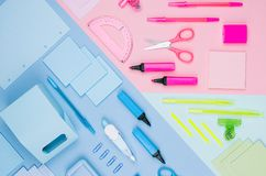 Назад к предпосылке школы - покрашенные различные канцелярские принадлежности установили на мягкое неоновое голубое, розовый, пре Стоковые Изображения RF