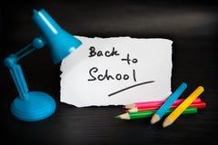 Назад к словам школы с меньшими лампой и карандашами на черной предпосылке Стоковые Изображения