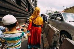 Назад матери женщины нося оранжевый поводок Hijab мальчик что носящ Takiyah на улице в Джакарте стоковое изображение rf